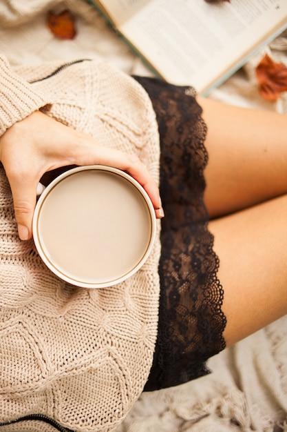 Een meisje in een warme trui zit op een beige wollen deken en houdt een mok warme koffie in haar handen. Premium Foto