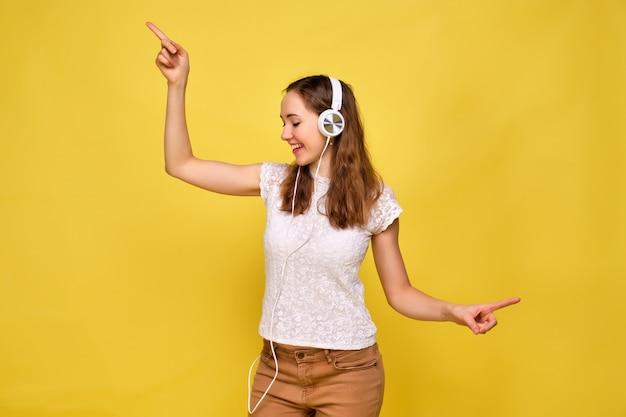 Een meisje in een wit t-shirt en bruine spijkerbroek op een gele achtergrond ontspant en danst luisterend naar muziek in witte koptelefoons. Premium Foto