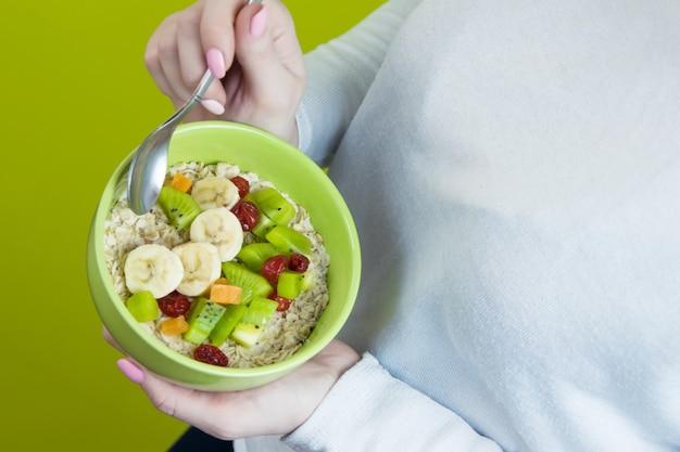 Een meisje in het wit houdt een bord havermout met fruit. bovenaanzicht Premium Foto