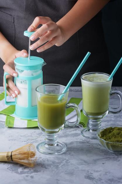 Een meisje klopt melk om een latte te maken van matcha groene thee. Premium Foto