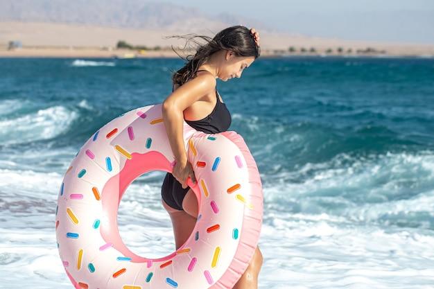 Een meisje met een donutvormige zwemcirkel aan zee. het concept van vrije tijd en vermaak op vakantie. Gratis Foto