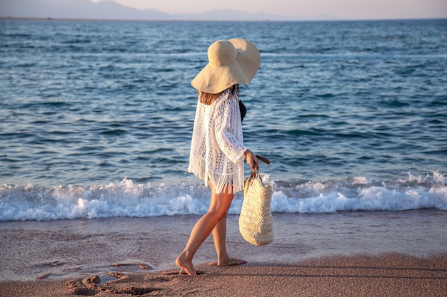 Een meisje met een grote hoed en een rieten tas loopt langs de zeekust. zomer vakantie concept. Gratis Foto
