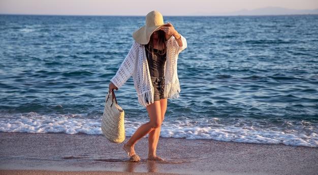 Een meisje met een grote hoed met een rieten tas loopt aan de kust. zomer vakantie concept. Gratis Foto
