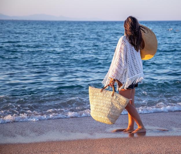 Een meisje met een hoed in haar handen en een rieten tas loopt aan de kust. zomer vakantie concept. Gratis Foto