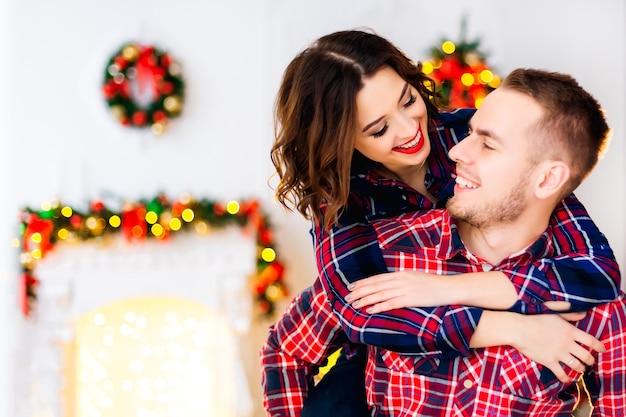 Een meisje met een mooie make-up die een man achter haar nek omhelst van achteren en hij kijkt haar aan en lacht. ze vermaken zich in de kamer met kerstversieringen Premium Foto