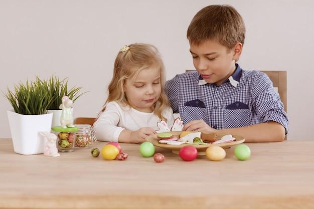 Een meisje met een oudere broer zit aan de vakantietafel en legt koekjes en paaseieren op Premium Foto