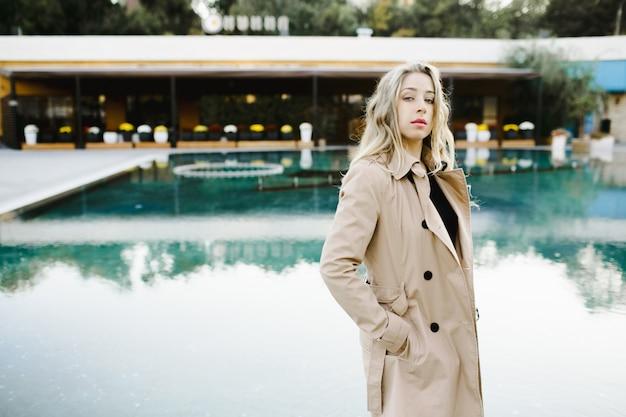 Een meisje staat bij een zwembad in een luxehotel Gratis Foto