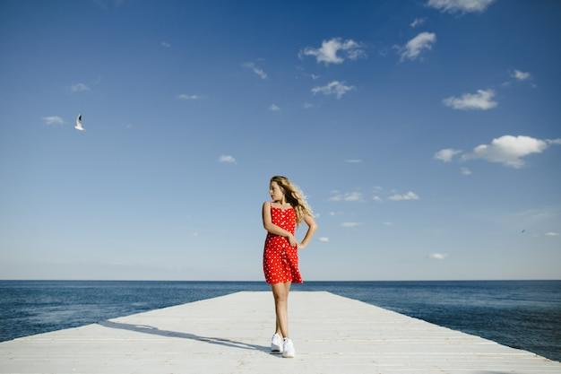 Een meisje staat op een ligplaats en kijkt naar zee Gratis Foto