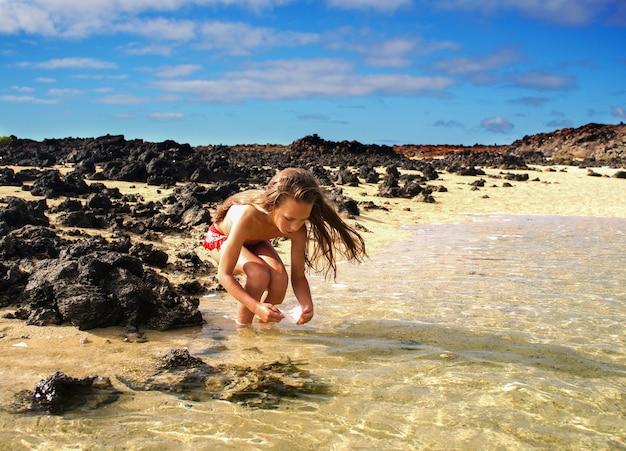 Een meisje van 10 jaar vis en krabben vangen, in het water aan de kust, oceaan Premium Foto