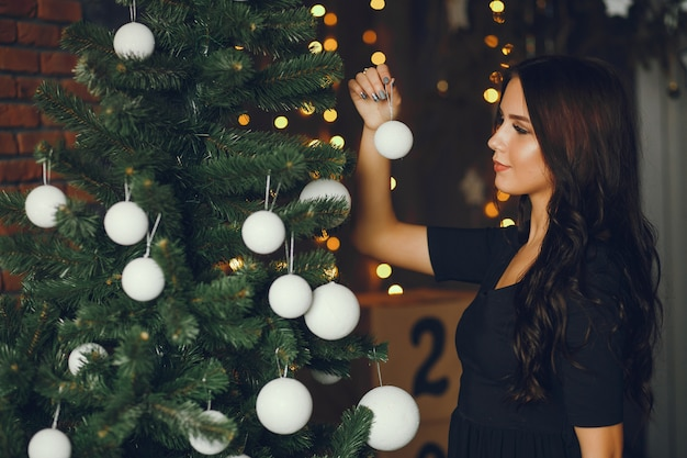 Een meisje versiert een kerstboom Gratis Foto