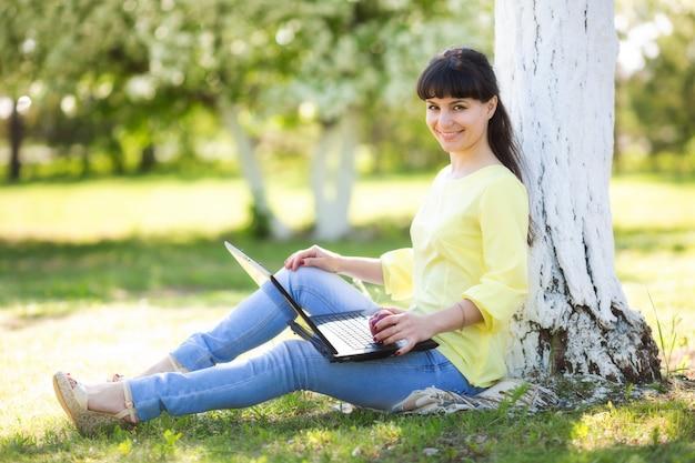 Een meisje zit met laptop dichtbij een boom. Premium Foto