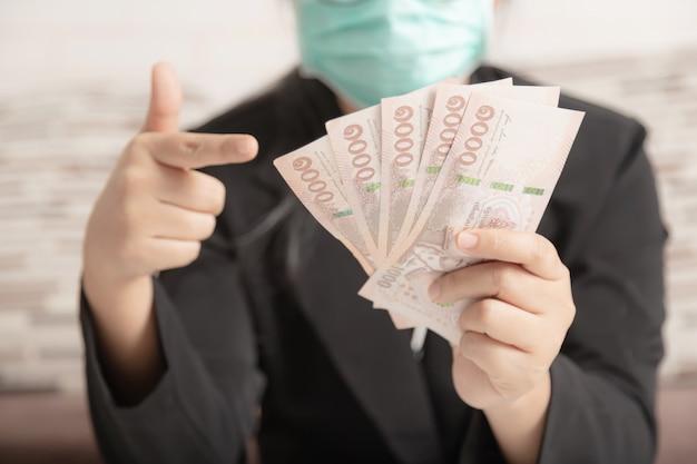 Een mens die een medisch masker draagt en een zwart pak dat het geld in haar hand richt. Premium Foto
