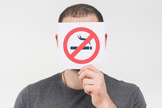 Een mens die geen rokend teken voor zijn gezicht houdt tegen witte achtergrond Gratis Foto