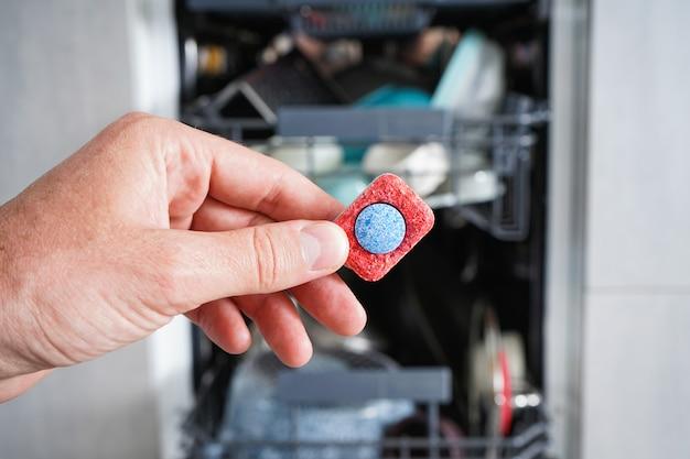 Een mensenhand die afwasmiddeltablet houden. Premium Foto