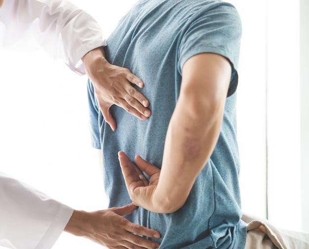 Een moderne revalidatiefysiotherapeut aan het werk met een man-cliënt Premium Foto