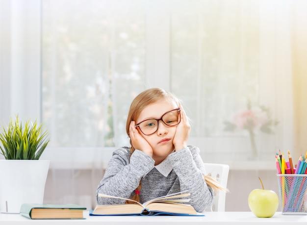 Een moe klein studentenmeisje zit aan een tafel met een stapel boeken. Premium Foto