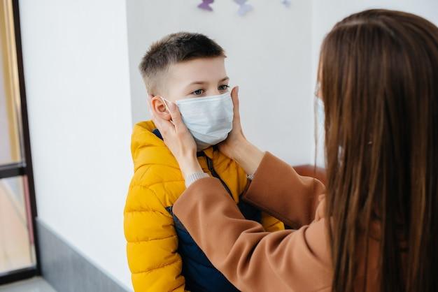 Een moeder met haar kind staat tijdens de quarantaine in een masker. pandemie, coronavirus. Premium Foto