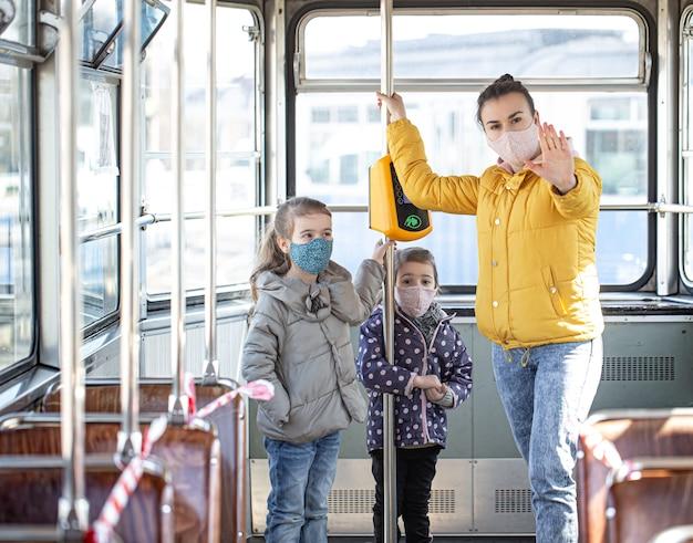 Een moeder met kleine kinderen die maskers draagt, beschermt zichzelf tegen coronavirus in het openbaar vervoer. Gratis Foto