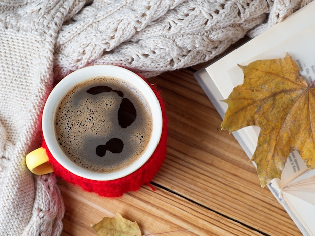 Een mok warme koffie met een warme wintertrui en een boek op tafel. winter samenstelling Premium Foto