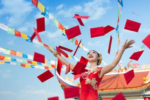Een mooi aziatisch meisje dat een rode kleding draagt Gratis Foto