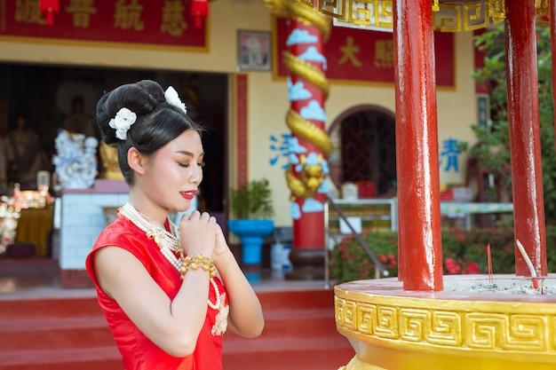 Een mooi aziatisch meisje dat een rode verering draagt Gratis Foto