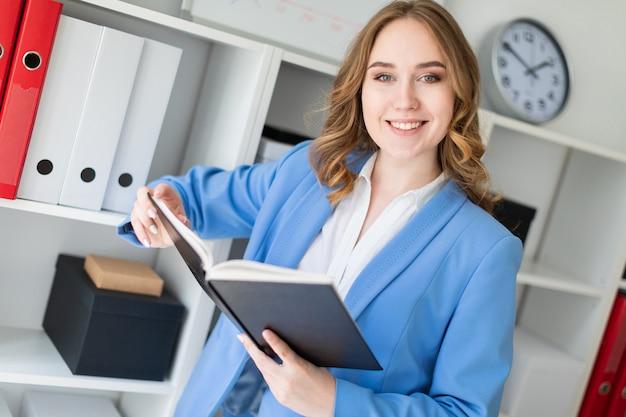 Een mooi jong meisje bevindt zich dichtbij een rek in het bureau en houdt een open boek in haar handen. Premium Foto