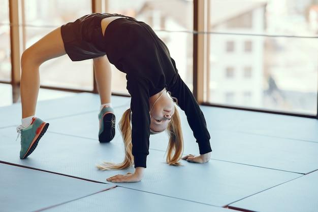Een mooi klein meisje is bezig met een sportschool Gratis Foto