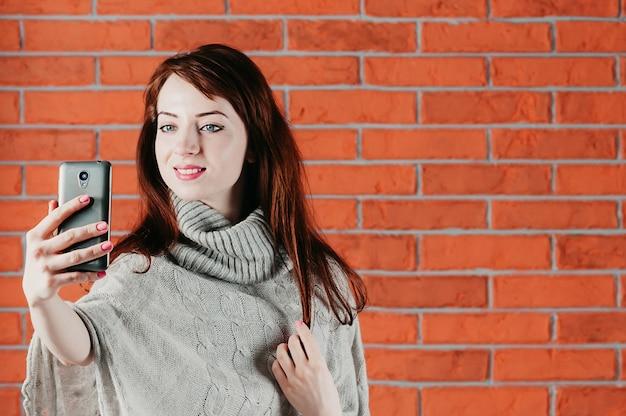 Een mooi meisje dat selfie maakt met een smartphone, glimlacht en een grijze trui draagt Premium Foto