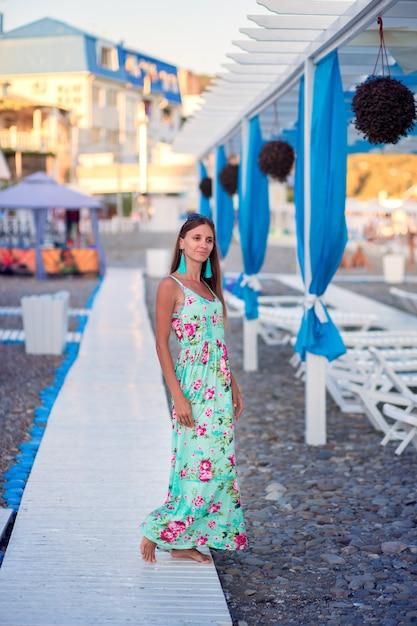 Een mooi meisje in een lange zomerjurk loopt langs een houten pad op een kiezelstrand aan zee in een toeristisch gebied Premium Foto