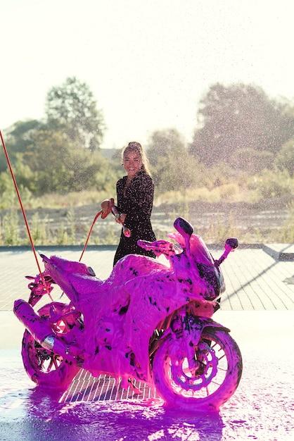 Een mooi meisje in een nauwsluitend verleidelijk pak wast een motorfiets en voelt zich gelukkig bij de autowasdienst. Premium Foto