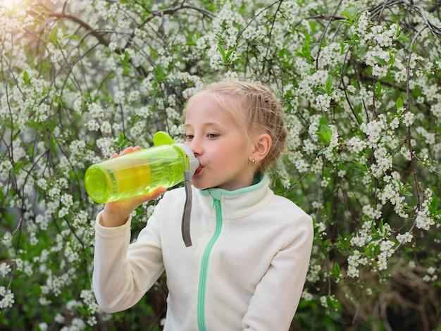 Een mooi meisje in het voorjaar park lest haar dorst met water met citroen en munt. Premium Foto