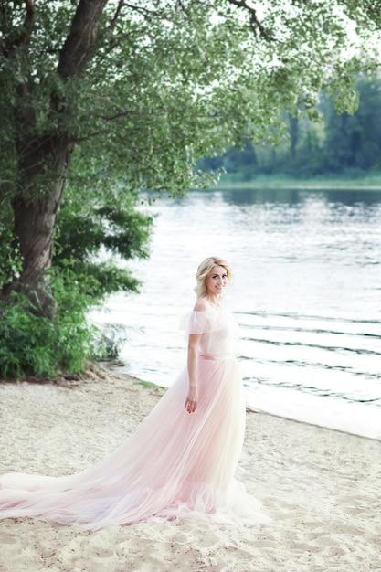 Een mooi meisje staat in een prachtige boheemse jurk op het strand. reizen en vrije tijd. vrijheid concept. mooie zomer vrouw op het strand. mooi meisje dat op het strand bij zonsopgang loopt. Premium Foto