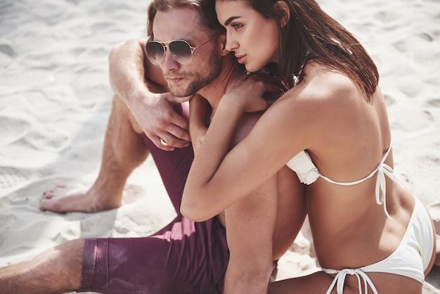 Een mooi paar dat op het zandstrand ontspant, in badkleding. romantische sfeer. Gratis Foto