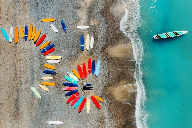 Een mooi stel ligt op het strand van frankrijk naast surfplanken, schietend vanuit een quadcopter, veel surfplanken liggen ongewoon op het strand. Premium Foto