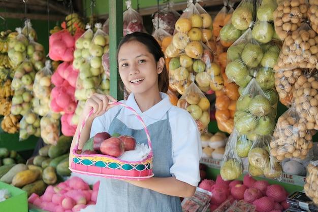 Een mooi winkelmeisje met fruit in een rieten mand voor een fruitpakket Premium Foto