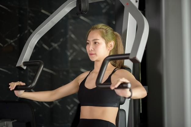Een mooie aziatische fitness vrouw traint met sportartikelen in de fitnessruimte. fitness- en gezondheidsconcept. Premium Foto