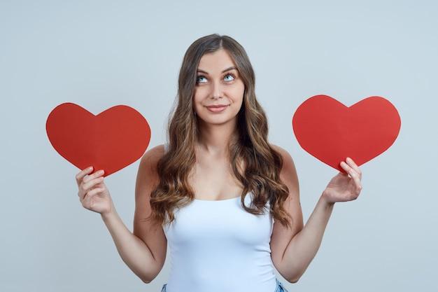 Een mooie blonde met krullen, houdt twee harten van papier vast, wordt opgezocht. fijne valentijnsdag. wereldhartdag. Premium Foto