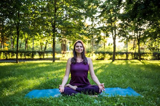Een mooie brunette meisje in een trainingspak zit op een blauwe yoga mat en kijkt naar de camera tegen op de zonsondergang in een open plek Premium Foto