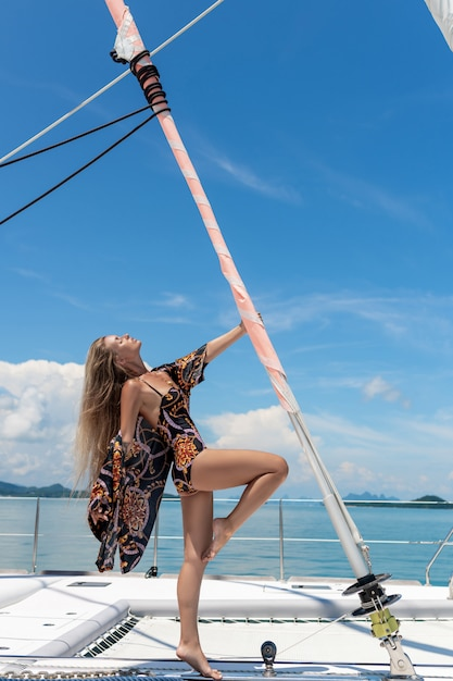 Een mooie, charmante blonde met lang haar in een gekleurd zwempak met een strandjas, poseren met één hand vasthoudend op een paal met een gedraaid zeil. jacht. rijke vakantie. Premium Foto