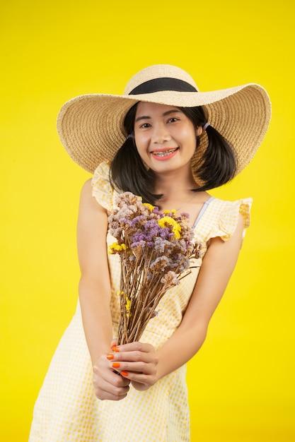 Een mooie, gelukkige vrouw die een grote hoed draagt en een boeket van gedroogde bloemen op een geel houdt. Gratis Foto