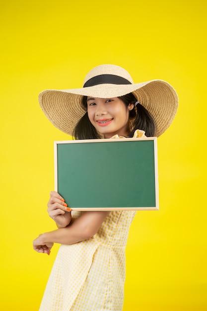 Een mooie, gelukkige vrouw die een grote hoed draagt en een groen bord op een geel houdt. Gratis Foto