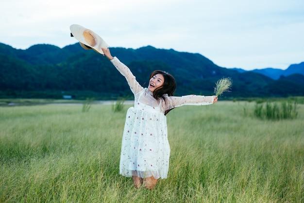 Een mooie, gelukkige vrouw gooit haar hoed op een prachtige weide en er is een berg in de. Gratis Foto