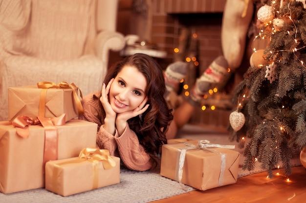 Een mooie glimlachende vrouw in een warme gebreide trui en sokken die dichtbij mooie kerstbomen en giften, het binnenland van het nieuwjaarhuis liggen Premium Foto