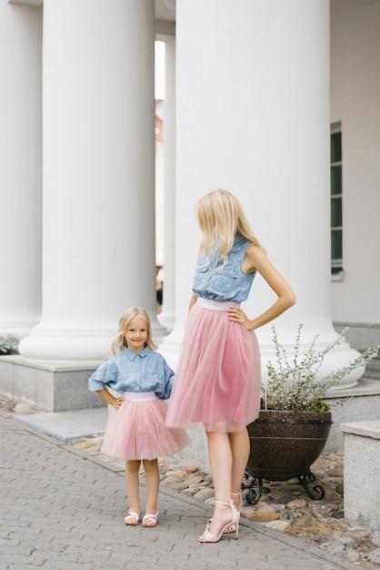 Een mooie jonge blonde moeder en haar charmante dochter in dezelfde romantische kleding staan bij de zuilen en glimlachen Premium Foto