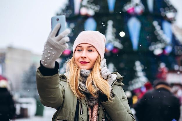 Een mooie jonge blonde vrouw lachend naar een telefoon voor een foto op de kerstmarkt Premium Foto