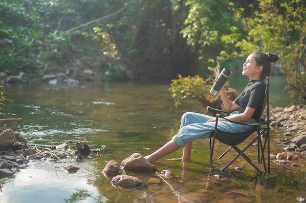 Een mooie jonge reiziger vrouw geniet met de natuur koffie te drinken in de ochtend boven het meer, ontspanning, kampeervakantie en reisconcept Premium Foto