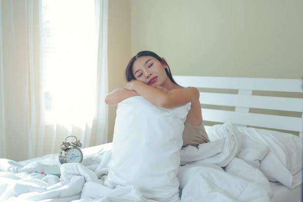 Een mooie jonge vrouw slaapt thuis en een wekker in de slaapkamer. Gratis Foto