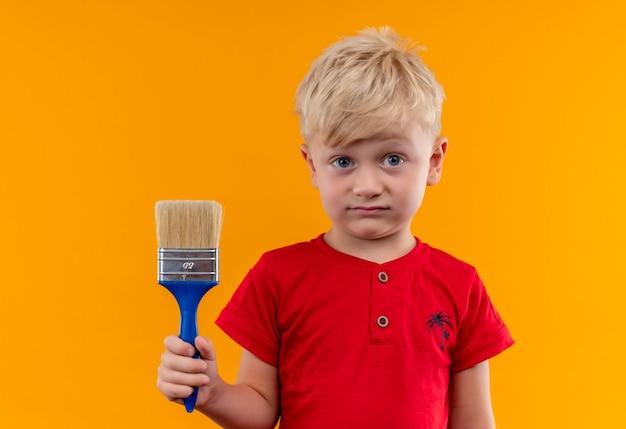 Een mooie kleine jongen met blond haar en blauwe ogen, gekleed in een rood t-shirt met blauwe verfborstel op zoek op een gele muur Gratis Foto