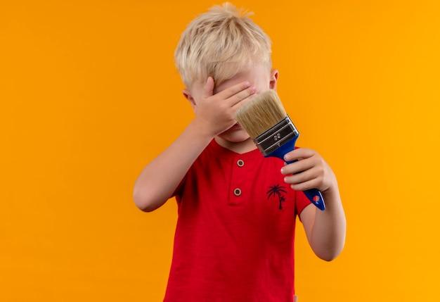 Een mooie kleine jongen met blond haar, gekleed in een rood t-shirt met blauwe verfborstel met hand bedekkende ogen op een gele muur Gratis Foto