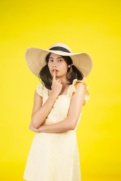 Een mooie, vrolijke jonge vrouw met een grote hoed op een geel. Gratis Foto